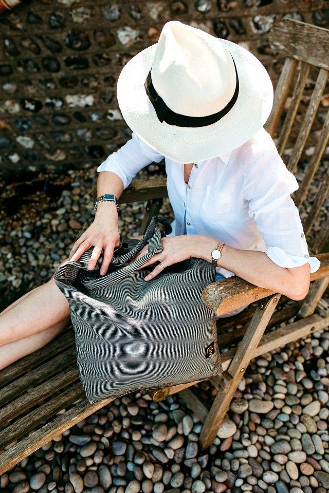 A fabric beach bag on a deckchair