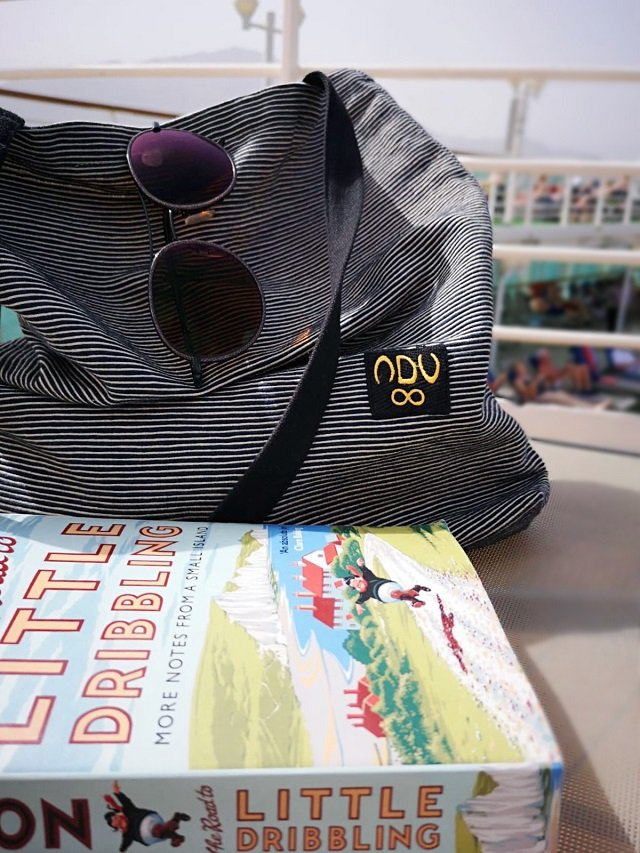 A tote bag on a cruise ship next to a book